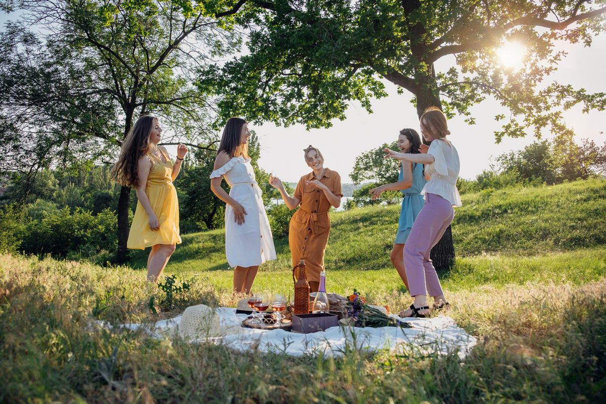 a group of friends standing in a green field by a picnic blanket